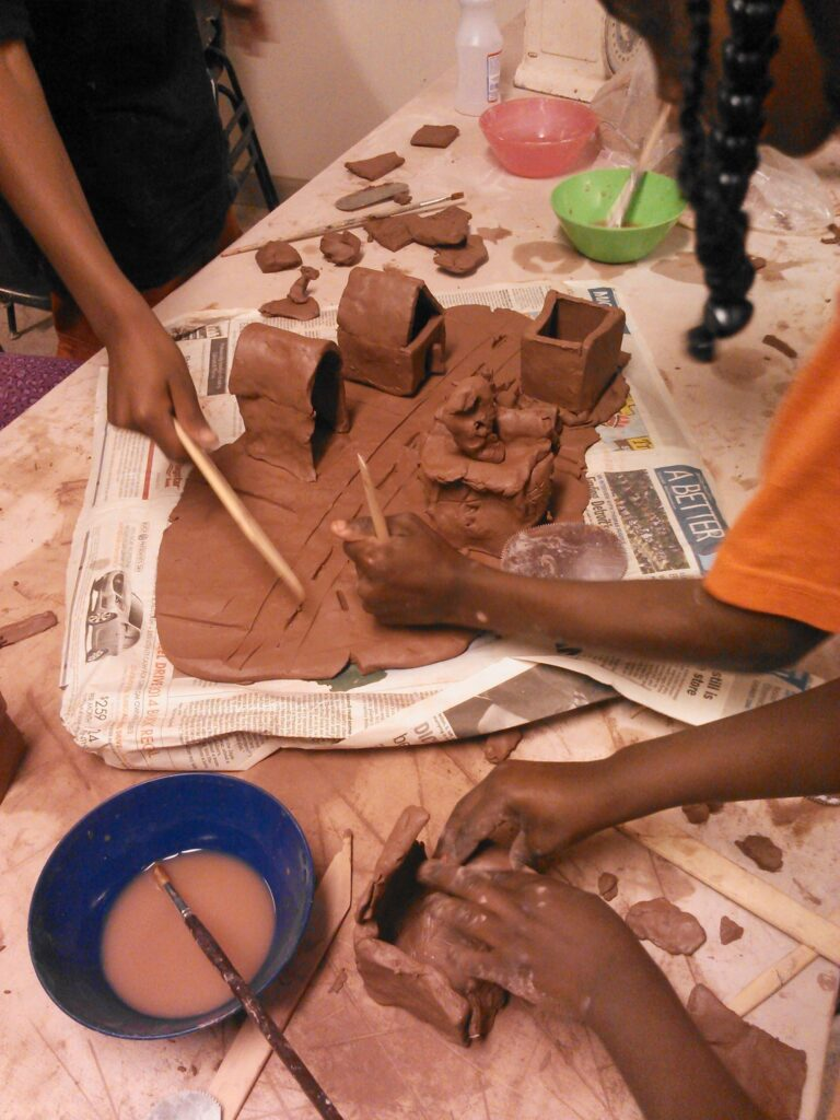 Students moulding a clay neighborhood