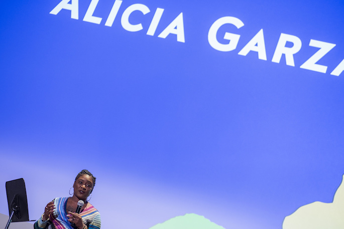 Alicia Garza speaking alone on stage in front of a blue backdrop at the opening ceremony of the 2017 AMC
