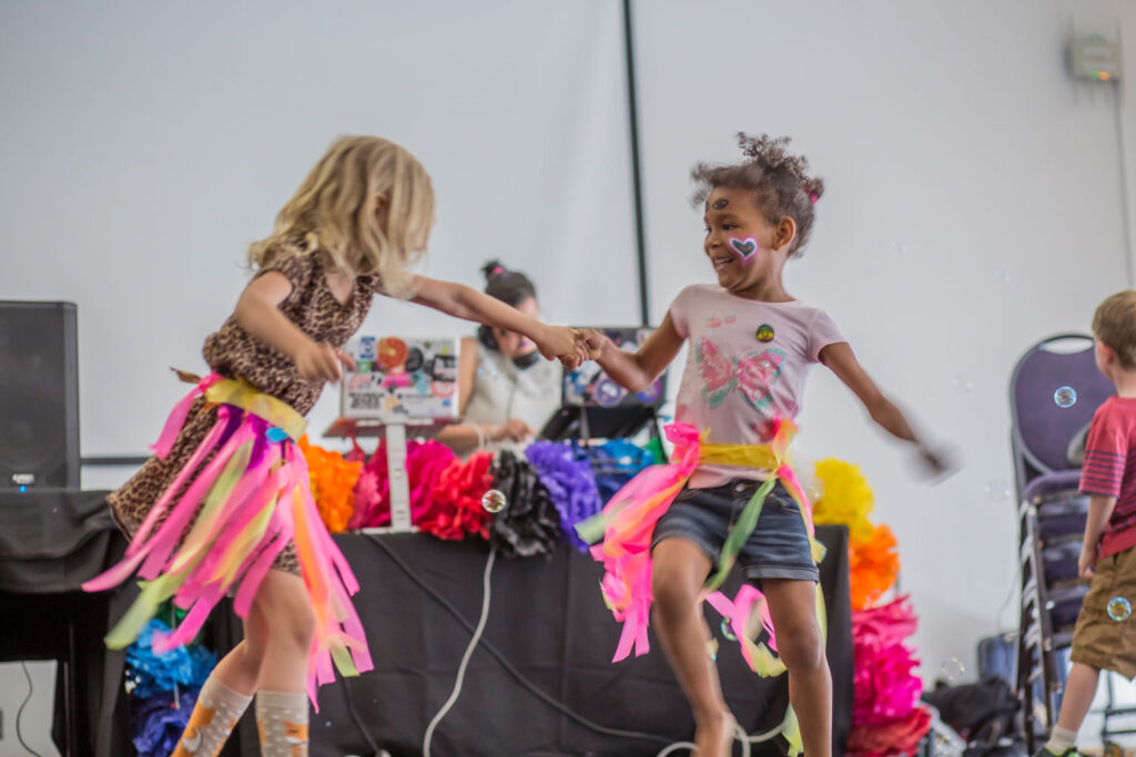 Two young children with facepaint and handmaid streamer skirts holding hands and dancing in front of a DJ table