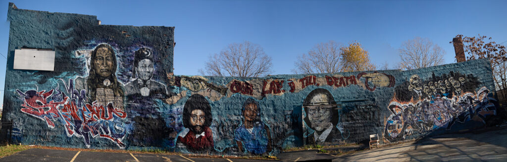 "A panorama picture of the mural titled ""Our Land Till Death Do Us Part"" on the full side of a long building featuring images of  Malice Green, Aiyana Stanley-Jones, Vincent Chin, Crazy Horse, and Elijah Muhammad"