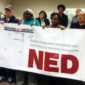 """Pixelated picture of four people holding a banner that says """"NED"""""""