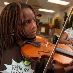 Young Black child playing a violin in a classroom