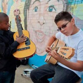 Two children playing guiter infront of a mural of the closeup of a child's face