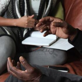 Closeup of hands gesturing, with another person sitting with a notebook on a table in the background