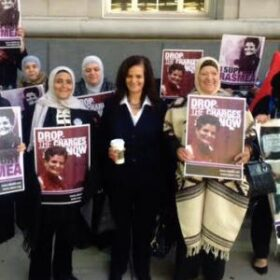 """A woman standing holding coffee next to other women holding signs of a person and the words """"Drop the charges now"""""""