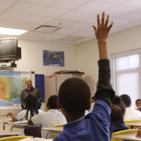 Image from behind a young Black student raising their hand with the teacher at the head of the class