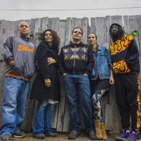 Long Hairz Collective members standing in front of a wooden fence