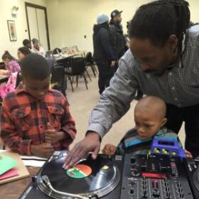 An adult and two children working with dj equipment
