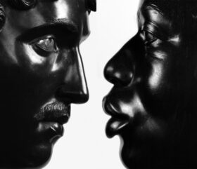 Close up of two sculptued black faces nearly touching each other