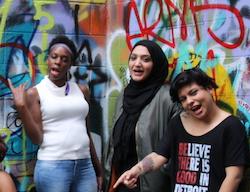 Three people infront of a graffiti wall
