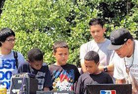 Children grouped around an adult showing them dj equipment