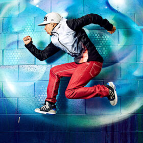 person dancing mid-air in front of a wall with a blue graffiti swirl