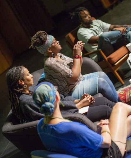 Photo of a panel discussion. Three people, one white, two Black, listen as a Black woman speaks to the audience
