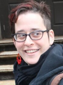 Headshot of Hannah Sassaman wearing red earrings and gray scarf