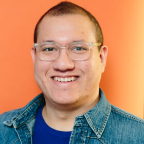 smiling light skinned Black and Asian man wearing a deep blue t-shirt under a denim button up on front of an orange background.
