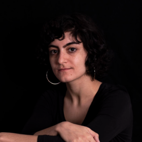A palestinian femme person with chin length dark hair, wearing black in front of a black background