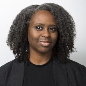 a black woman with shoulder-length hair wearing a black shirt and blazer in front of a grey background0