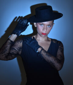 a femme person wearing dark gloves, a lace shirt, dark tilted hat, and red lipstick stands before a blue background