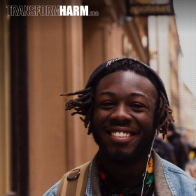 """Portrait photo of a young black man on a city sidewalk, smiling with headphones with the headline text """"TranformHarm.org"""""""