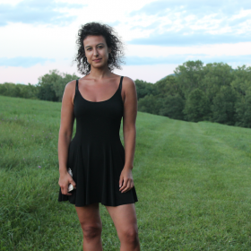 A brown-skinned woman stands toward the left of the frame wearing a fitted black sleeveless dress that cuts mid-way across her thighs. She has black curly hair and looks at the camera with a slight smirk. Behind her is a landscape with a sloping hill covered in lush green grass and a bright blue sky dotted with fluffy white clouds.